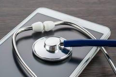 Doktorsarbetsplats med den digitala tableten och stetoskopet Arkivfoto