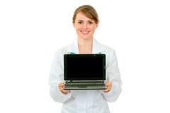 doktorsbärbar datorläkarundersökning som visar den le kvinnan Fotografering för Bildbyråer