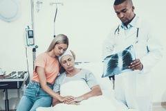 Doktorsblickröntgenstråle Kvinna med modern cancer royaltyfria bilder