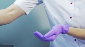 Doktorscosmetologist i det medicinska laget som sätter på handskar i en skönhetsalong isolerad medicinsk white för bakgrund sjukv stock video