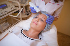 Doktorscosmetologisten gör tillvägagångssättet en kvinna på framsidan av Spa royaltyfri foto