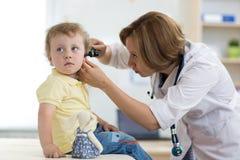 Doktorscy egzamininuje dziecka ` s ucho w doktorskim ` s biurze obrazy royalty free