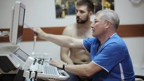 Doktorscy pokazuje rezultaty ultradźwięku diagnostyk na ekranie sonogram przyrząd zbiory wideo