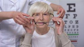Doktorscy proponuje przechodzić na emeryturę dam nowi eyeglasses, zadowolona cierpliwa odwiedza okulistka zdjęcie wideo
