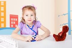 doktorsflicka little som leker Hon behandlar en nallebjörn royaltyfri foto