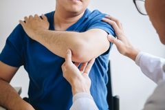 Doktorsfysioterapeut som hjälper en manlig patient, medan ge sig öva behandling som masserar armen av patienten i ett physio rum, royaltyfri fotografi