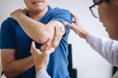 Doktorsfysioterapeut som hjälper en manlig patient, medan ge sig öva behandling som masserar armen av patienten i ett physio rum, royaltyfri foto