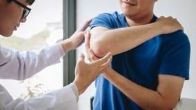 Doktorsfysioterapeut som hjälper en manlig patient, medan ge sig öva behandling som masserar armen av patienten i ett physio rum, royaltyfria foton