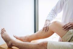 Doktorsfysioterapeut som hjälper en manlig patient, medan ge sig öva behandling som masserar benet av patienten i ett physio rum, royaltyfri foto