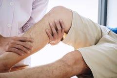 Doktorsfysioterapeut som hjälper en manlig patient, medan ge sig öva behandling som masserar benet av patienten i ett physio rum, royaltyfri bild