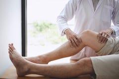 Doktorsfysioterapeut som hj?lper en manlig patient, medan ge sig ?va behandling som masserar benet av patienten i ett physio rum, arkivfoton