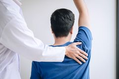 Doktorsfysioterapeut som hj?lper en manlig patient, medan ge sig ?va behandling som masserar skuldran av patienten i ett physio fotografering för bildbyråer