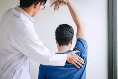 Doktorsfysioterapeut som hj?lper en manlig patient, medan ge sig ?va behandling som masserar skuldran av patienten i ett physio royaltyfria bilder