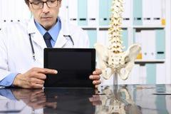 Doktorshänder som pekar den digitala minnestavlan på skrivbordet royaltyfri fotografi