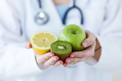 Doktorshänder som rymmer frukt liksom äpplet, kiwi och citronen royaltyfri foto