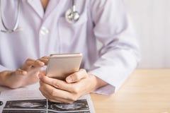 Doktorshand genom att använda den smarta telefonen, medan arbeta på sjukhuset arkivbilder