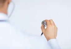Doktorshand med stetoskopet som lyssnar något Arkivbild