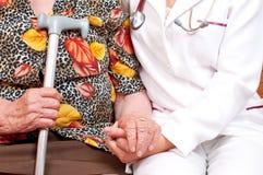 doktorshand som rymmer den gammala s-kvinnan Arkivbild