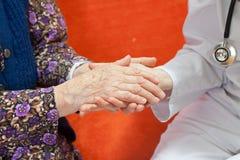 doktorshanden rymmer den gammala söta kvinnan för s ung Arkivfoto