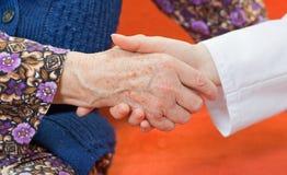 doktorshanden rymmer den gammala söta kvinnan för s ung Arkivbilder