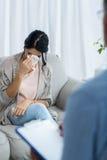 Doktorshandstil på skrivplattan, medan konsultera gravida kvinnan Arkivfoto