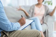 Doktorshandstil på skrivplattan, medan konsultera gravida kvinnan Royaltyfri Bild