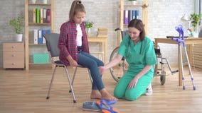 Doktorshjälp i rehabilitering som sträcker benet med hjälpen av en rulle av en tonårs- flicka i en rullstol arkivfilmer
