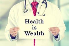 Doktorshänder som rymmer det vita korttecknet med hälsa, är rikedomtextmeddelandet Royaltyfri Fotografi