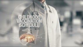 Doktorsinnehav i schema för handbarndomvaccinering Royaltyfria Bilder