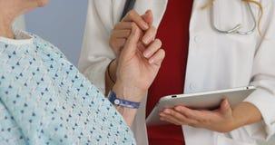 Doktorsinnehavhand av den mogna kvinnan i sjukhussäng arkivfoto