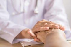 Doktorsinnehavhand och trösta den gamla patienten i ett sjukhus arkivbild