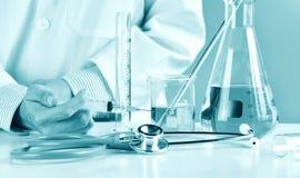 Doktorsinnehavinjektionsspruta med den medicinska vaccinen, laboratoriumglasföremål royaltyfria bilder