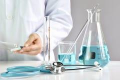 Doktorsinnehavinjektionsspruta med den medicinska vaccinen, laboratoriumglasföremål royaltyfri bild