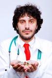 Doktorsinnehavmynt i hans händer arkivfoton