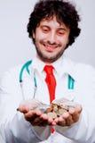 Doktorsinnehavmynt i hans händer och le Royaltyfri Fotografi