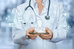 Doktorsinnehavtelefon med den manliga doktorn på skärmen royaltyfria bilder