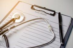 Doktorska czek lista z stetoskopem i piórem zdjęcia stock