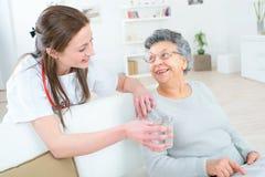 Doktorska daje starej damy szkła woda Zdjęcia Royalty Free