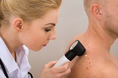 Doktorska egzamininuje pigmentowana skóra Zdjęcia Royalty Free