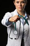 Doktorska kobieta daje stetoskopowi odizolowywającemu na czerni Obraz Stock