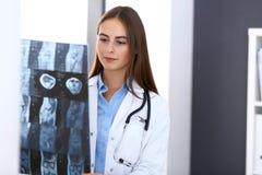 Doktorska kobieta egzamininuje promieniowanie rentgenowskie obrazek podczas gdy stojący blisko okno w szpitalu Chirurg lub ortope zdjęcia royalty free
