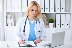 Doktorska kobieta przy pracą Portret rozochocony uśmiechnięty blondynka lekarz używa pastylka komputer przy biurkiem podczas gdy  zdjęcie stock