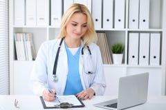 Doktorska kobieta przy pracą Portret rozochocony uśmiechnięty blondynka lekarz używa pastylka komputer przy biurkiem podczas gdy  fotografia stock