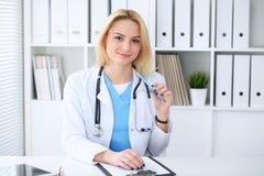 Doktorska kobieta przy pracą Portret rozochocony uśmiechnięty blondynka lekarza obsiadanie przy biurkiem Medycyny i opieki zdrowo obraz stock