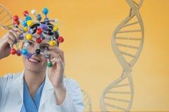 Doktorska kobieta trzyma medyczną postać z 3D DNA pasemkiem przeciw żółtemu tłu Fotografia Royalty Free