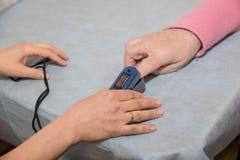 Doktorska miara krwionośnego tlenowego pacjenta na łóżku z oximeter Sprzęt medyczny Doktorski używa pulsu oximeter czujnik na obrazy royalty free