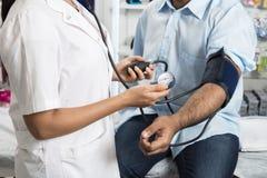 Doktorska mienie tarcza Obsługuje ` s ciśnienie krwi Podczas gdy Pomiarowy zdjęcia royalty free