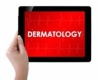 Doktorska pokazuje pastylka z dermatologia tekstem zdjęcia stock
