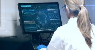 Doktorska przyglądająca dna molekuła na komputerze zbiory