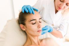 Doktorska sprawdza kobiety ` s skóra przed chirurgią plastyczną obraz stock